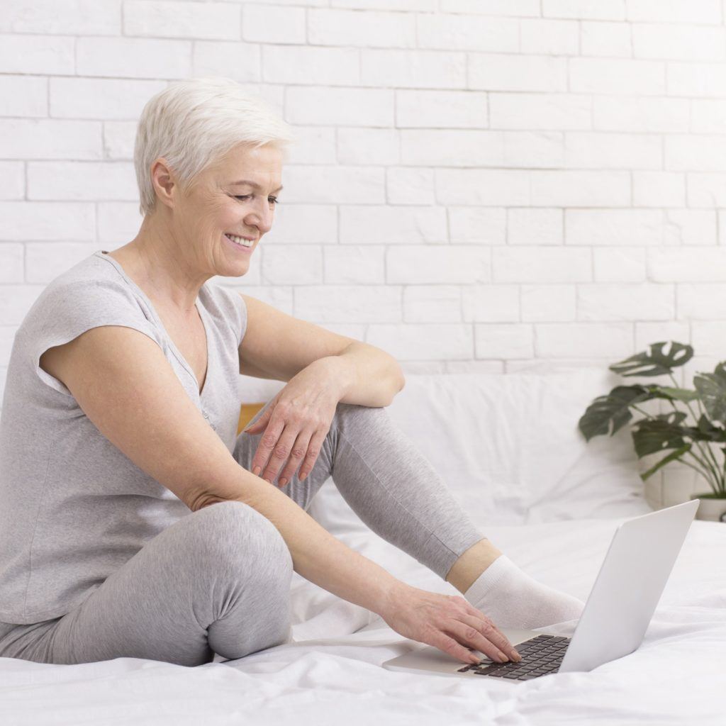 Cheerful senior lady enjoying internet on laptop at home